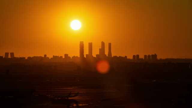 vídeos y material grabado en eventos de stock de timelapse of the sun passing behind the four towers in madrid - madrid