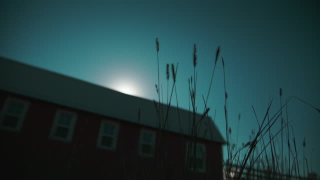 Timelapse of the sun rising from behind a barn with grass in the foreground