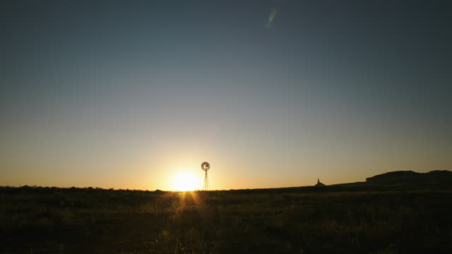 vidéos et rushes de timelapse of the sun rising on the prairie with a silhouetted windmill and chimney rock national historic site - grandes plaines américaines