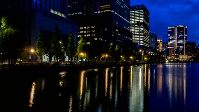 4K timelapse of Tokyo Cityscape with skyscrapers and office buildings illuminated reflection in Hibiya, Marunouchi, Otemachi, Tokyo station aera, Japan at night.
