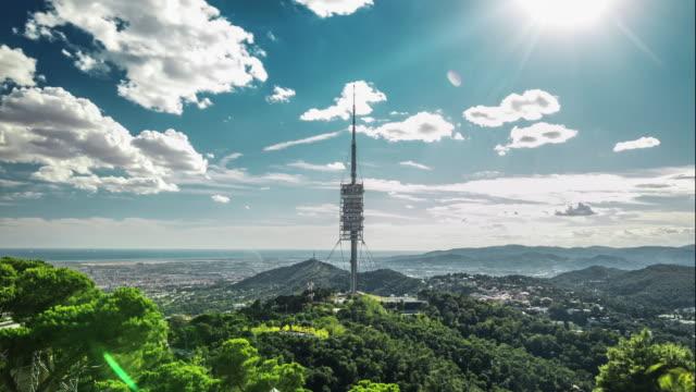 vídeos de stock e filmes b-roll de timelapse of torre de collserola from tibidabo mountain, barcelona, spain. - cadeia de montanhas