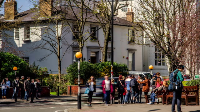 time-lapse of tourists/fans crossing the famous abbey road, london. - the beatles stock videos & royalty-free footage