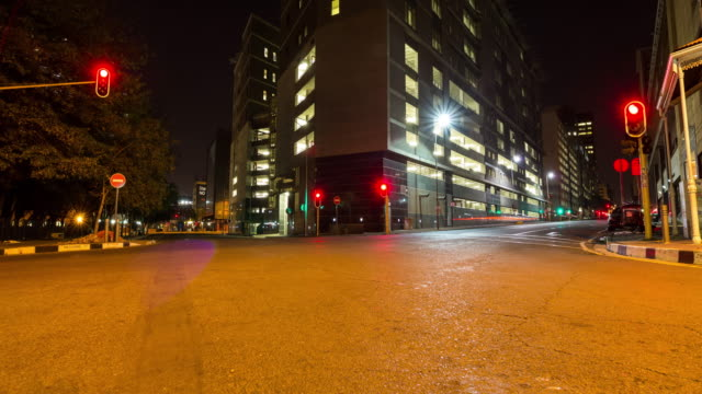 timelapse of traffic lights flickering green and red with cars driving past in the city centre of johannesburg - ecke eines objekts stock-videos und b-roll-filmmaterial