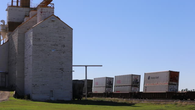 time-lapse of train passing a grain barn - prairie stock videos and b-roll footage