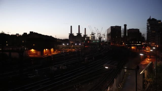 timelapse of trains passing the battersea power station at dawn in battersea london united kingdom on wednesday december 10 2014 - バタシー発電所点の映像素材/bロール