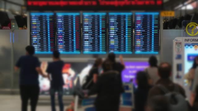 timelapse of traveller crowd at airport departure board - blackboard stock videos & royalty-free footage