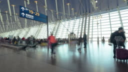 4K UHD Time-lapse of unidentified people walking in airport transit terminal. Air transportation, international tourism, travel abroad, or commuter lifestyle concept