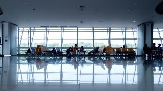 Time-Lapse verschiedener Nationalität Passagiere warten und Wandern im Gate terminal am Flughafen