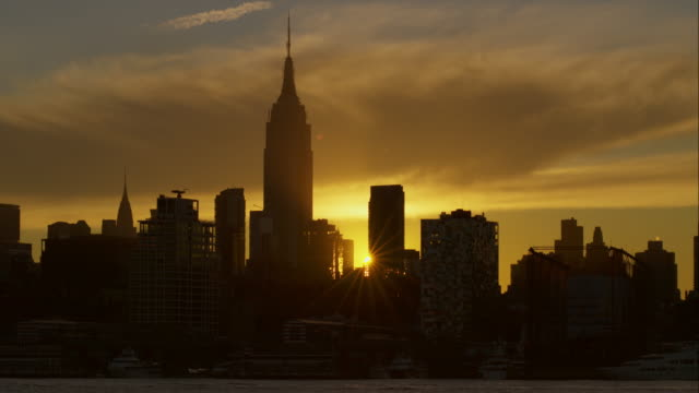 Timelapse of vibrant sunrise above the Empire State Building in New York City seen from across the Hudson River