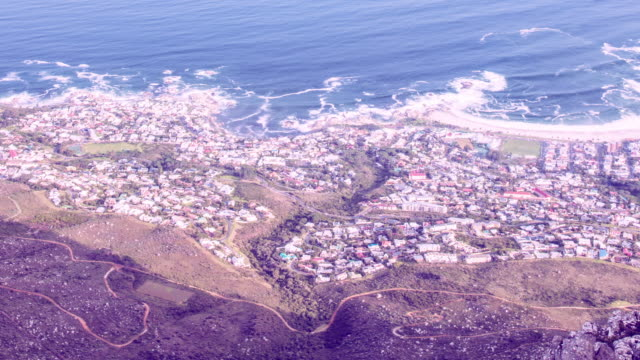 stockvideo's en b-roll-footage met timelapse of view from table mountain to clifton beach in cape town, south africa. waves crashing on the beach, cars driving along the coastal road. view of miniature town - table top view