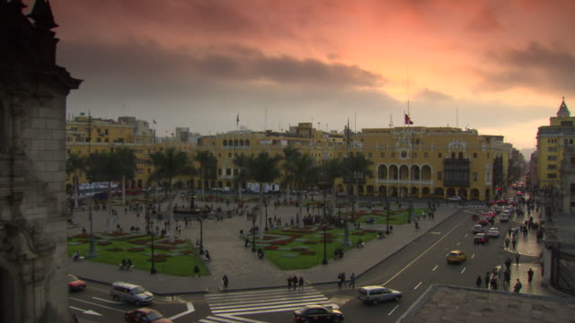 'Timelapse of View from top of building at corner of Plaza Mayor/Plaza de la Armas of Lima towards The Municipal Palace of Lima [Municipalidad Metropolitana de Lima] and the Palace of the Union, peach and orange sky, Lima, Peru'