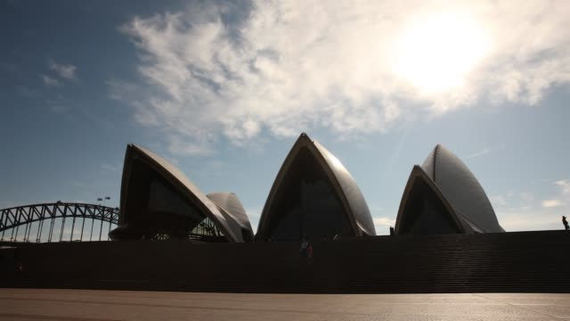 timelapse of visitors at the sydney opera house as the sun shines through a blue sky and passing clouds in sydney australia on friday july 3 2015 - bennelong point stock videos and b-roll footage