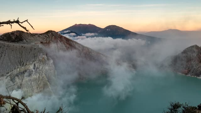 time-lapse of volcano an active with sulfur smoke in turquoise lake in morning at kawah ijen, indonesia - zumare indietro video stock e b–roll