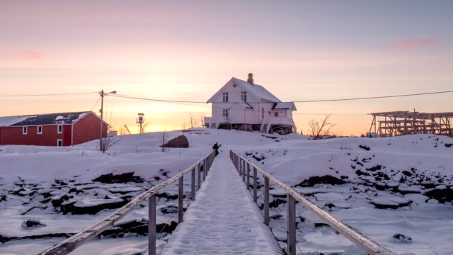 Time-lapse of White house with wooden bridge and frozen coastline at morning sunrise