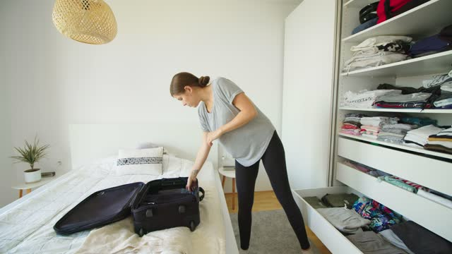 time-lapse of woman putting clothes away in the closet - luggage stock videos & royalty-free footage