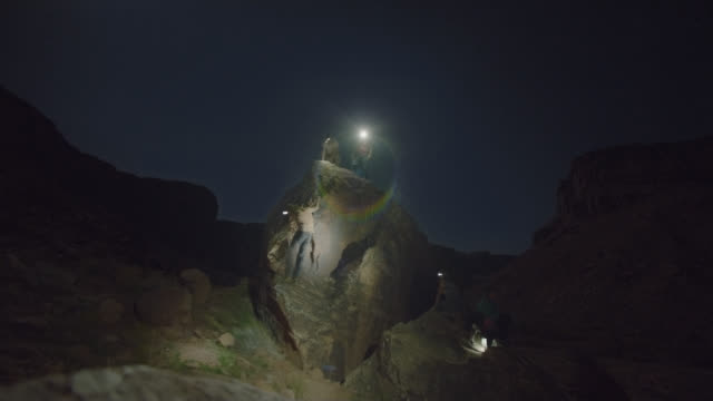 timelapse of young adventurers with headlamps bouldering in moab at night. - wilderness stock videos and b-roll footage