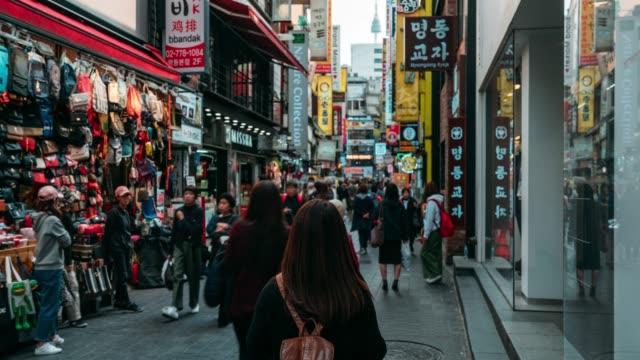vídeos y material grabado en eventos de stock de timelapse del viajero asiático joven viajando y de compras en el mercado de la calle myeong-dong en seúl, corea del sur. barrio myeong dong es el mercado comercial más popular en la ciudad de seúl. - seúl