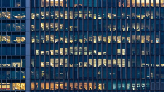 time-lapse office window night in london canary wharf england uk - edificio adibito a uffici video stock e b–roll