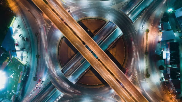time-lapse or hyper-lapse aerial view 4 way road stop circle or intersection traffic at night for transportation concept. - roundabout stock videos & royalty-free footage
