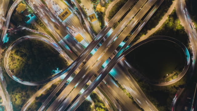time-lapse or hyper-lapse aerial view highway road roundabout circle or intersection traffic at night for transportation concept. - time stock videos & royalty-free footage