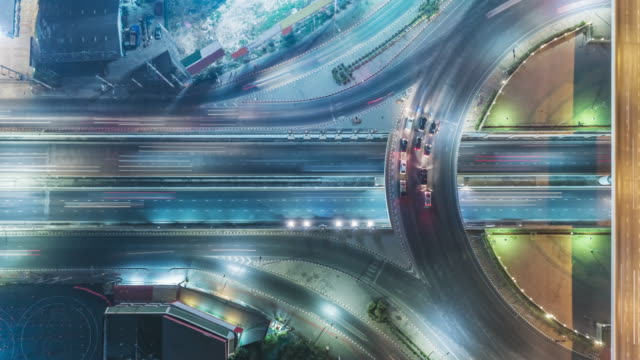 time-lapse or hyper-lapse aerial view highway road roundabout circle or intersection traffic at night for transportation concept. - tramway stock videos & royalty-free footage