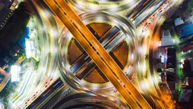 time-lapse or hyper-lapse aerial view highway road roundabout circle or intersection traffic at night for transportation concept. v - 線路のポイント点の映像素材/bロール