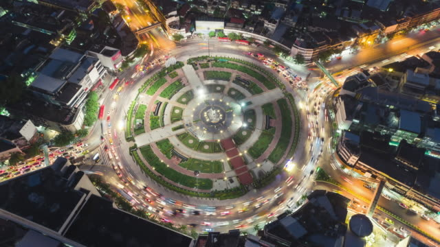 vídeos de stock e filmes b-roll de time-lapse or hyper-lapse zoom in aerial view 4 way road roundabout circle or intersection traffic at night for transportation concept. - rotunda entroncamento