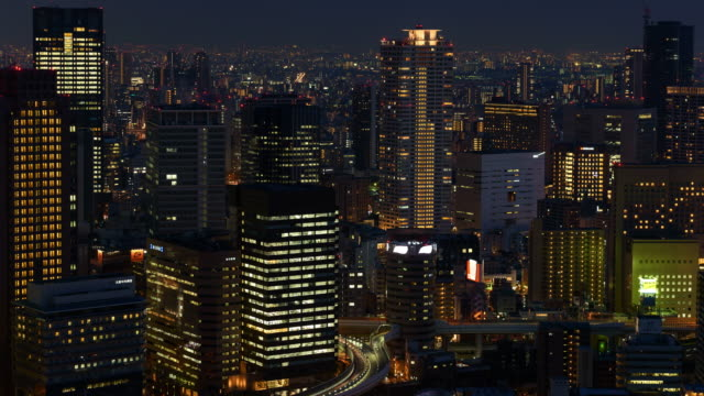 k time-lapse: osaka cityscape at night with tollway and illuminated building - osaka stock videos and b-roll footage