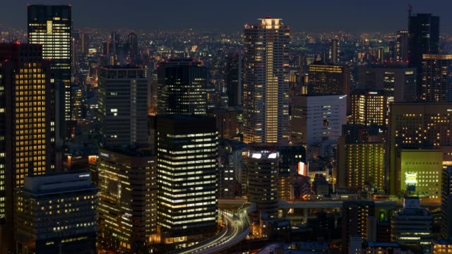 4k time-lapse: osaka cityscape at night with tollway and illuminated building, zoom in shot - zoom in stock videos & royalty-free footage