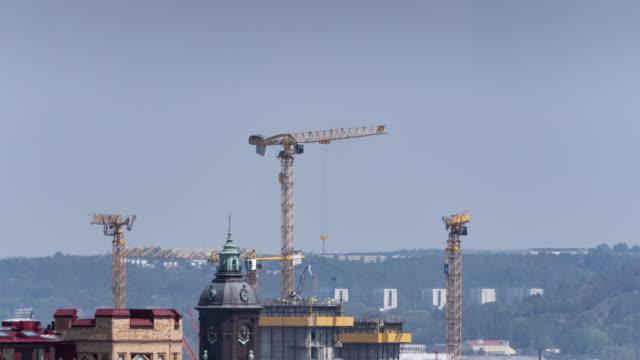 vídeos de stock, filmes e b-roll de timelapse sobre o cityscape de gothenburg com os guindastes que constroem a casa - imperfeição