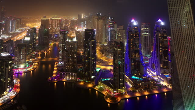 Timelapse pan over skyscrapers, traffic and Dubai Marina at night, UAE