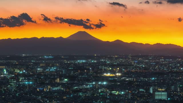 4kタイムラプス:東京の首都都と山富士の背景で、夜の夜景と高層ビルの夜景を放置したパンニング - 連続するイメージ点の映像素材/bロール