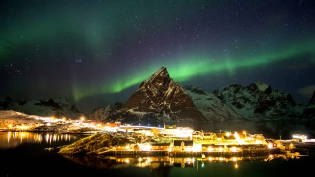 time-lapse panning of aurora borealis over mountain with scandinavian rorbuer in winter at night - pole stock videos & royalty-free footage