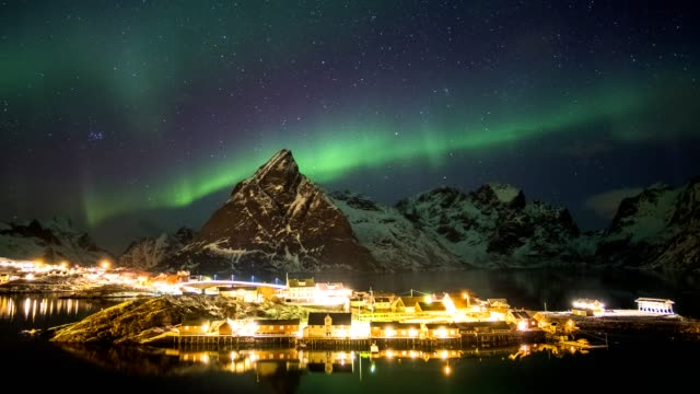 time-lapse panning of aurora borealis with starry over mountain with scandinavian village on winter - alternative energy stock videos and b-roll footage