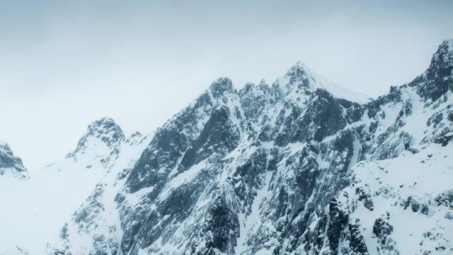 vídeos de stock, filmes e b-roll de time-lapse panorâmica do topo da montanha com nevasca em sombrio no inverno - nevasca