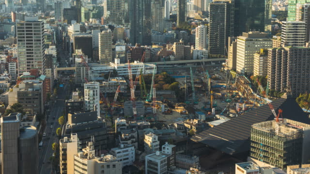 4k time-lapse: panning right in view of cranes working in site construction in tokyo city japan - execution stock videos & royalty-free footage