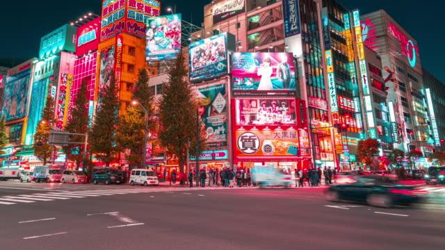vídeos y material grabado en eventos de stock de 4k time-lapse: panning derecho de peatonal lleno de gente y compras turísticas en la ciudad eléctrica de la calle del barrio de akihabara para videojuegos, anime en tokio por la noche - cultura japonesa