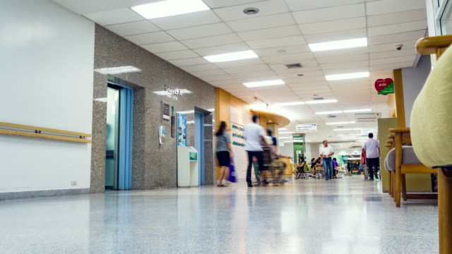 timelapse, patients moving in the corridor at the hospital. - esposizione lunga video stock e b–roll