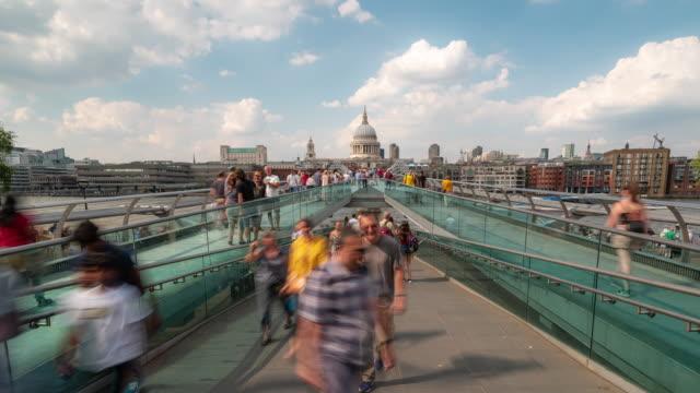 vídeos y material grabado en eventos de stock de time-lapse: pedestrian commuter crowd en millennium bridge con st paul's cathedral en londres, inglaterra, reino unido - el milenio