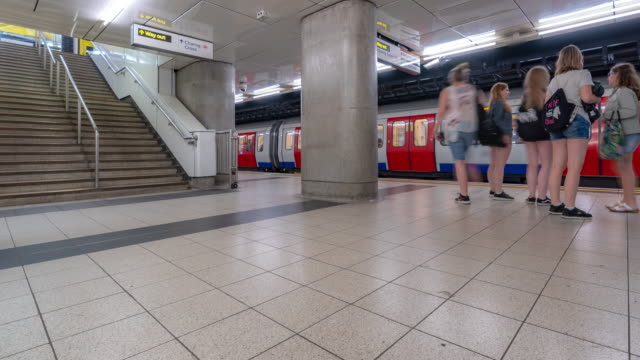 time-lapse: pedestrian commuter crowd at subway tube platform in london england uk - railings stock videos & royalty-free footage