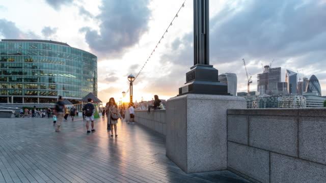 zeitraffer: fußgänger pendler menschenmenge auf tower bridge und die city hall in london england uk - rathaus stock-videos und b-roll-filmmaterial