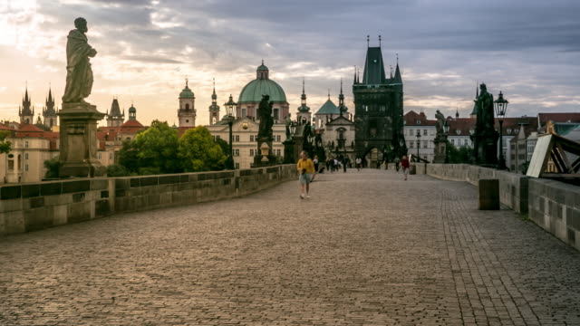 4k time-lapse: pedestrian crowded charles bridge karluv most czech sunrise - prague bridge stock videos and b-roll footage