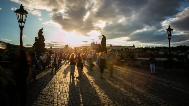 4k time-lapse: pedestrian crowded charles bridge karluv most czech sunset - czech republic stock videos & royalty-free footage