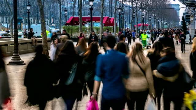 vidéos et rushes de hd time-lapse:  zone touristique de foule de champs-élysées, à paris en soirée - société de consommation