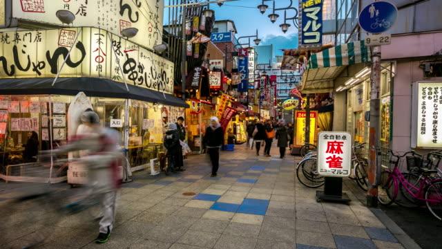 Zeitraffer: Fußgänger Einkaufen bei Tsutenkaku Tower Shinsekai Osaka Japan