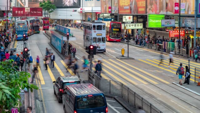time-lapse: pedestrians tourist with historic  tram in background at causeway bay  hong kong - causeway stock videos & royalty-free footage