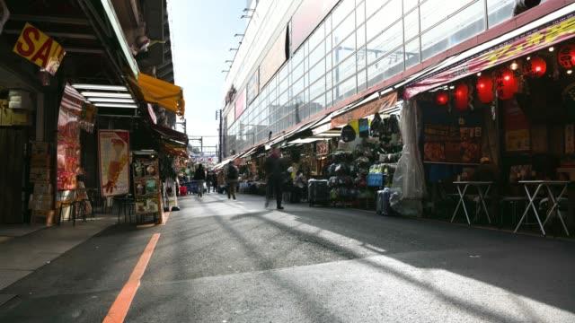 Zeitraffer: Fußgänger zu Fuß und einkaufen auf der Ameyoko Straßenmarkt Tokio Japan