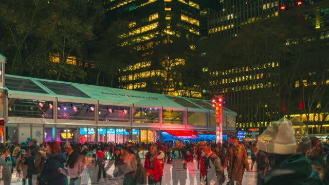 4k time-lapse people are enjoying ice skating at bryant park new york in dusk at christmas holidays season during the winter. local vendors also set up market stalls in the park during the winter. - bryant park stock videos & royalty-free footage