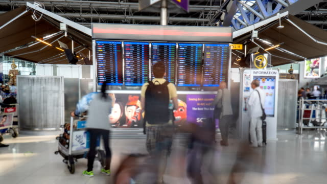 timelapse 4k - people checking arrival departure board - scrutiny video stock e b–roll