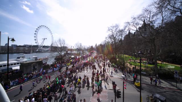 timelapse people stream around course during london marathon, uk - london marathon stock videos & royalty-free footage